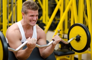 Handsome young man training biceps lifting barbell on bench in a gym
